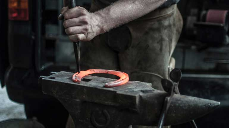 A farrier forging a horseshoe on a hose job