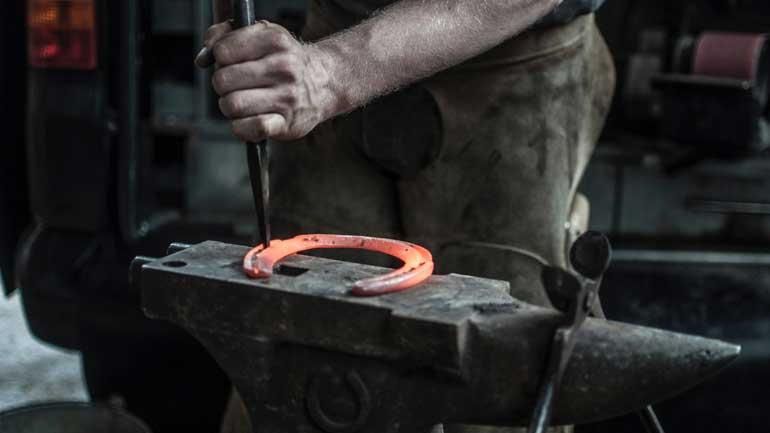 A farrier forging a horseshoe on a hose job